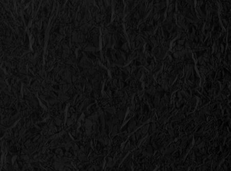 Dark crumpled black paper background or texture