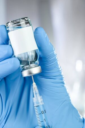 Healthcare concept with a hand in blue medical gloves holding a vaccine vial with blue liquid and black white label Stock fotó