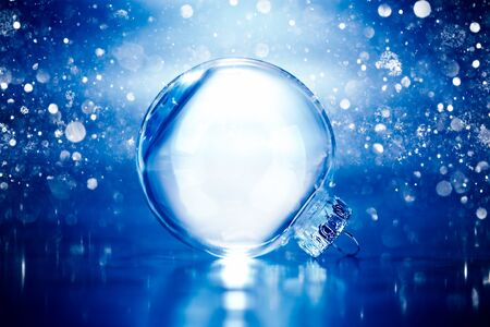 Clear glass Christmas ornament on blue glittering lights background with blank empty space 版權商用圖片