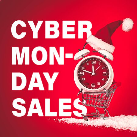Cyber Monday Sales text with Christmas Santa hat on red clock, balanced in shopping cart with snow.