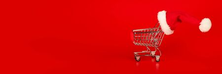 Shopping cart with Christmas Santa hat on red background. Xmas shopping concept. 版權商用圖片