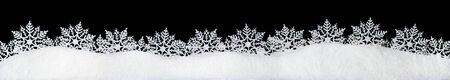 Banner of sparkling fuffy white snow with snowflakes isolated on black