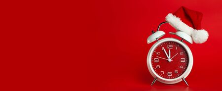 Red clock with Christmas Santa hat. Time for Christmas shopping concept. Blank red space for text.
