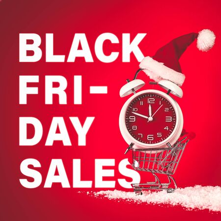 Black Friday Sales text with Christmas Santa hat on red clock, balanced in shopping cart with snow. 版權商用圖片