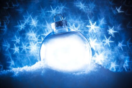 Clear Christmas ornament in snow surrounded by a bokeh of glittering lights in the shape of snowflakes. 版權商用圖片