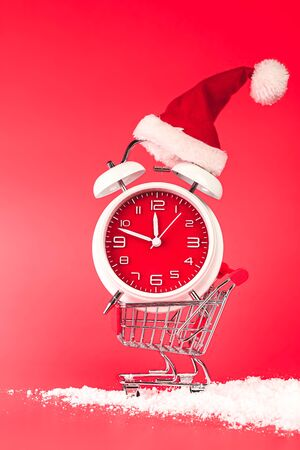 Christmas Santa hat on red clock, balanced in shopping cart. Last minute Christmas shopping concept with blank empty space for text.