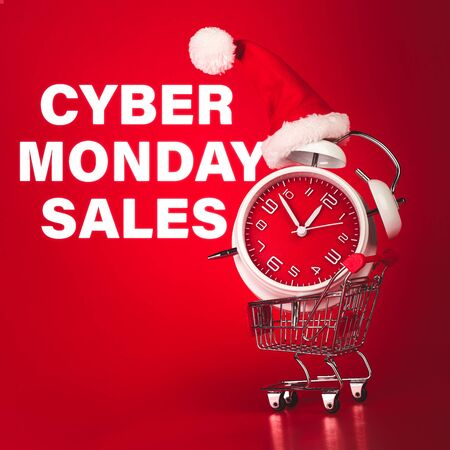 Cyber Monday Sales text with Christmas Santa hat on red clock, balanced in shopping cart. 版權商用圖片