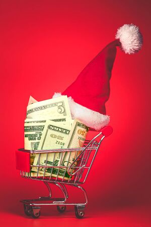 Christmas Santa hat on shopping cart full of money. Xmas cash gift, or chrismas spending concept.