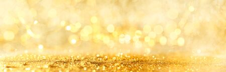 Abstract bokeh of glowing yellow lights and sparkling gold glitter background or wallpaper 版權商用圖片