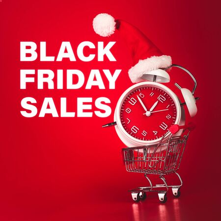 Black Friday Sales text with Christmas Santa hat on red clock, balanced in shopping cart.