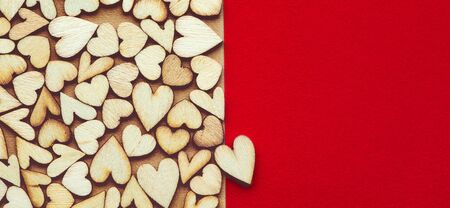 Romantic  of dozens of tiny wooden hearts with a single heart on a red card.