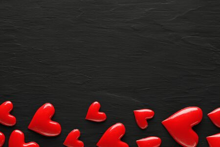 Collection of shiny red hearts on dark rough background