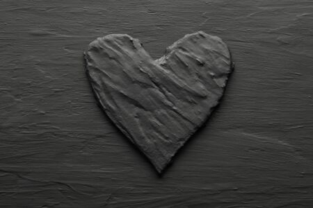 Dark black heart on rough slate like bakcground