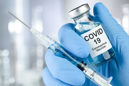 Healthcare cure concept with a hand in blue medical gloves holding Coronavirus, Covid 19 virus, vaccine vial Standard-Bild