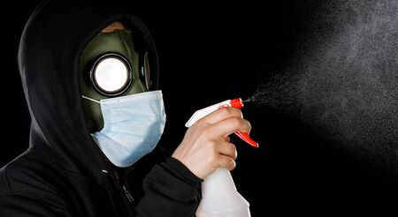 Person wearing old hazmat style gas mask and medical mask cleaning with spray bottle.