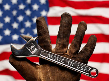Old worn work glove holding adjustable wrench with Made in USA text. American workforce or industry, or America labor concept.