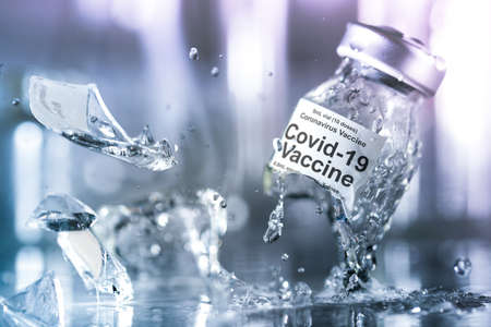 Coronavirus vaccine vial breaking into pieces with splashing liquid. Failure to create a vaccine, find a cure for the corona virus, or the dangers of an untested drug concept.