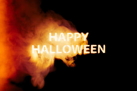 Happy Halloween text glowing like a jack o lantern in smoke and fire.