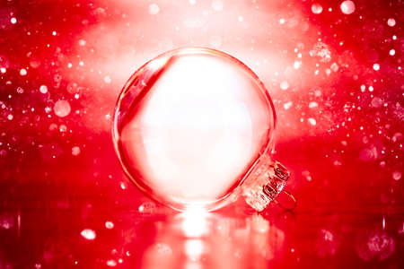 Clear glass Christmas ornament on red glittering lights background with blank empty space