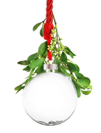 Clear Christmas ornament hanging by red ribbon rope with the bauble surrounded with green mistletoe.
