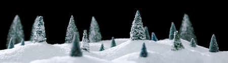 Wintry forest scene of miniature snow covered trees on glittering snow drifts isolated on black