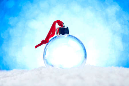 Clear empty Christmas ornament with red ribbon sitting in snow with shiny blue lights bokeh background
