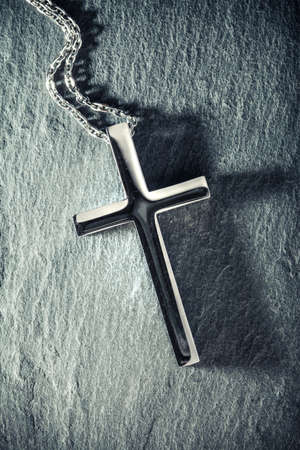 Christian cross necklace on slate background with the crucifix casting a dark shadow. 版權商用圖片