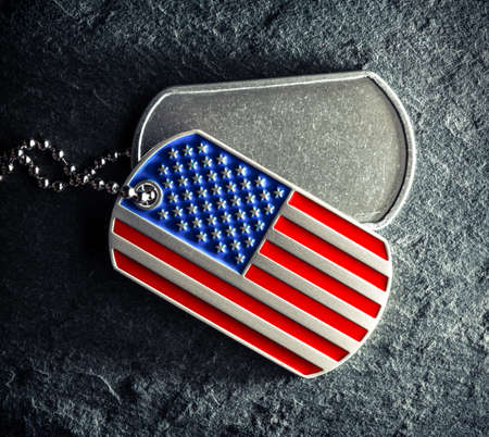 US military soldier's dog tags, rough and worn with blank space for text, and in the shape of the American flag. Memorial Day for Veterans Day concept.