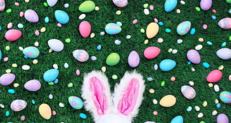 Bright and colorful Easter eggs and candy with pink bunny ears