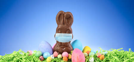 Chocolate Easter bunny wearing a medical mask surrounded by painted Easter eggs and colorful decorations. 版權商用圖片