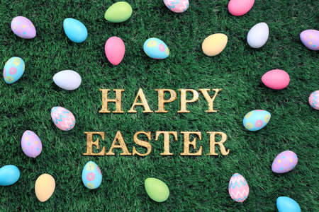 Gold Happy Easter text surrounded with colorful Easter eggs on grass