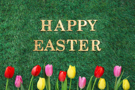 Happy Easter text on green grass with colorful tulips.