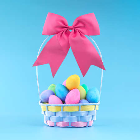 Easter basket for Easter egg hunt filled with colorful painted Easter eggs, topped with a pink bow.