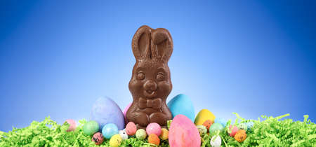 Happy chocolate Easter bunny surrounded by painted Easter eggs and colorful decorations.