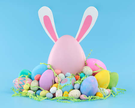 Large pink Easter egg with bunny ears surrounded by a pile of colorful Easter eggs and candy. 版權商用圖片