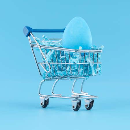 Blue Easter egg in shopping cart for Easter shopping concept. 版權商用圖片