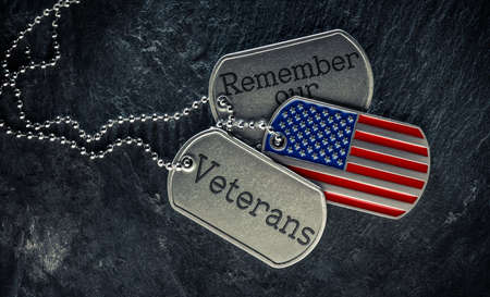 US military soldier's dog tags engraved with Remember our Veteran's text and in the shape of the American flag. Memorial Day or Veterans Day concept. 版權商用圖片