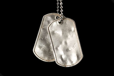 Old and worn blank military dog tags isolated on black 版權商用圖片