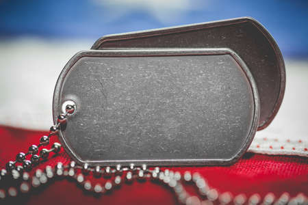 Worn USA military dog tags close up on US American flag with blank space for text