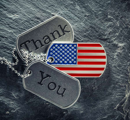 US military soldier's dog tags engraved with Thank You text and in the shape of the American flag. Memorial Day or Veterans Day concept.
