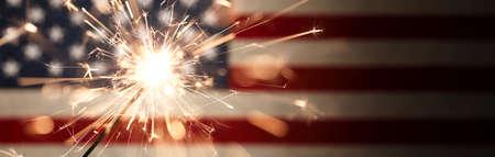Sparks flying off a burning sparkler in front of the US American flag for patriotic 4th of July celebration. 版權商用圖片
