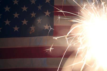 Lit sparkler burning in front of American Flag 版權商用圖片
