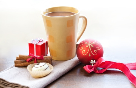 Christmas morning and new year  Cup of hot chocolate with cinnamon sticks, candy, Christmas ball and small box present on wooden table photo