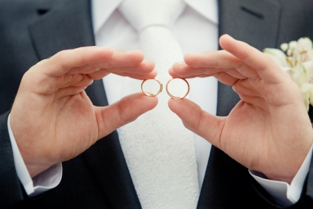 groom holding a gold rings photo
