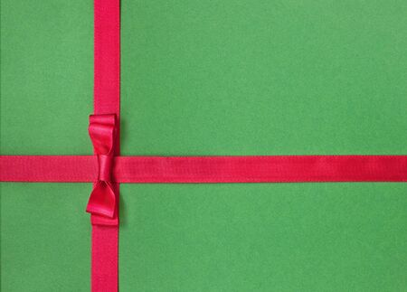 Red satin ribbon with bow on green background  photo