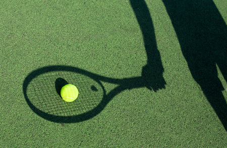 in action on a tennis court (conceptual image with a tennis ball lying on the court and the shadow of the player positioned in a way he seems to be playing it) Фото со стока