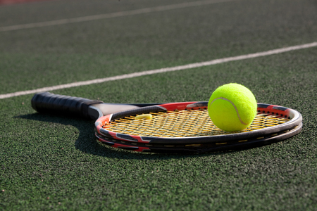 tennis racket with a ball on court
