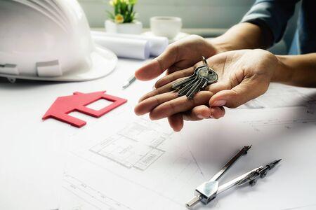 cerrando negocio: Female hand holds keys on blueprint,Construction concept. Engineering tools.Vintage tone retro filter effect,soft focus(selective focus)