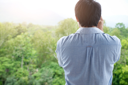 The young man looking at the beautiful view with soft morning light. Relaxing concept.    Stock Photo