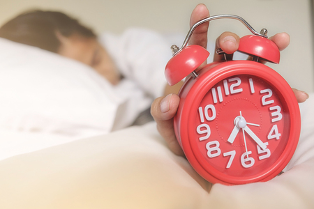 Irritated young woman putting her alarm clock off in the morning with soft morning light. Relaxing concept.